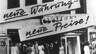 """Kundenandrang vor einem Geschäft, das nach der Währungsreform 1948 Schilder mit der Aufschrift """"Neue Währung... neue Preise!"""" an der Hausfassade angebracht hat."""
