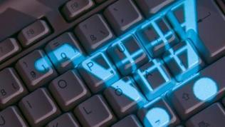 Das Symbol eines Einkaufskorbs leuchtet auf einer Computertastatur.