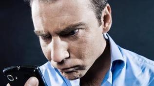 Mann schaut ungläubig auf sein Smartphone
