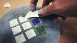 Mit dem Cuttermesser das doppelseitige Klebeband von den Mosaiksteinen entfernen.