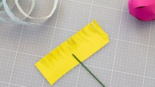 Ein Rechteck von ca. 10x2cm zurechtschneiden. Mit einer Schere senkrechte Schnitte ganz dicht nebeneinander setzen, ohne sie abzuschneiden.