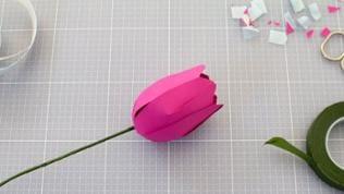 Stiel durch die Blüte hindurchstecken. Vorher Kreis als Markierung für das Loch machen, mit spitzen Gegenstand einstechen. Wenn der Tulpenkopf sehr wackelt, innen auf das Loch Flüssigkleber auftragen.