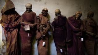 Sechs Mumien stehen an einer weißen Wand in der Kapuzinergruft in Palermo