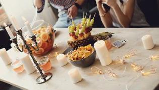 Mit Bowle, Obstspießen und Taccos gedeckter Wohnzimmertisch bei einer Party