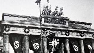 The Brandenberg gate in the German captial, Berlin. Taken during the Second World War, Nazi flags are shown hanging from the famous monument. Dated 1940.
