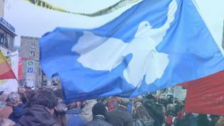 Eine Fahne mit einer Friedenstaube weht beim Ostermarsch in Stuttgart.