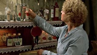 Bea räumt Schnapsflaschen ins Regal im Hofladen