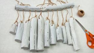 Holzstücke mit weißer Farbe streichen und durchbohren, auch das lange Holz. Jedes Stück am Bildfaden anknoten und durch langes Holzstück fädeln. An äußeren Löchern Faden für die Aufhängung anknüpfen.
