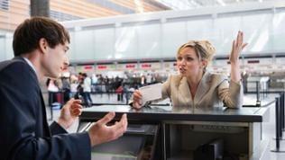 Eine Frau steht mit ihrem Flugticket an einem Schalter