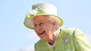 Queen Elizabeth lacht vor blauem Himmel und trägt einen extravaganten Hut