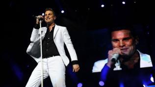 Eloy de Jong im weißen Anzug mit schwarzem Hemd auf der Bühne. Im Hintergrund auf der LED-Wand ein Live-Ausschnitt.