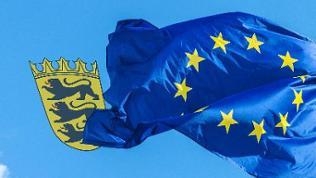 Eine wehende Europaflagge und ein Baden-Württemberg Wappen
