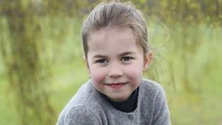 Die britische Prinzessin Charlotte sitzt mit Rock und Pullover auf einer Wiese