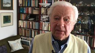 Philipp Münch steht vor Bücherregal