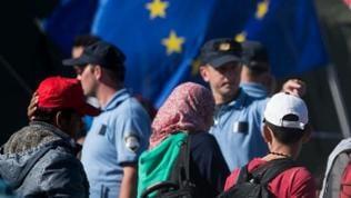 Flüchtlinge mit Kopftuch oder Kappe vor der Europaflagge mit Grenzsoldaten