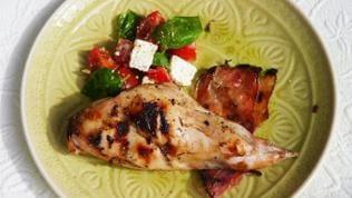 stück gegrilltes Kaninchen mit Tomatensalat, basilikum und schafskäse mit einem Stück bacon