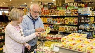 Älteres Paar steht im Supermarkt mit einer Packung Eier in der Hand