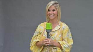 Sängerin Beatrice Egli steht mit grünem SWR4 Mikrofon vor einer grauen Wand und lächelt