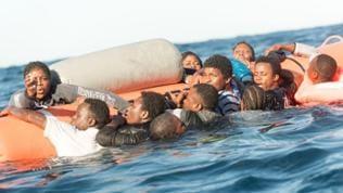 Flüchtlinge, die auf Booten von Libyen nach Italien übersetzen wollten, klammern sich während eines Rettungseinsatzes am 27.01.2018 vor der libyschen Küste an einen Rettungsschlauch