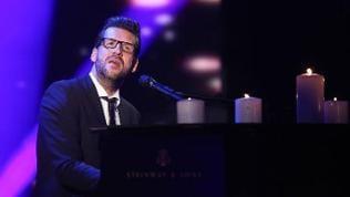 Sänger André Stade sitzt in einem schwarzen Anzug an einem Klavier auf dem Kerzen stehen und singt.