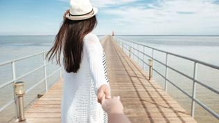 Frau geht auf Steg zum Meer