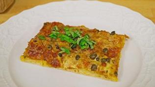 eckiges stück Pizza mit olivenstückchen und grünen Kräutern auf weißem teller