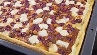 Pizza auf Blech mit Kirschen und mandeln und schmand-klecksen