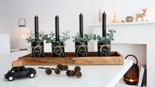 Etwas Grün, wie Moos oder Eucalyptus um die Kerzen herum stecken. Alle vier Dosen auf das Holztablett stellen und wer es gern üppiger mag, kann das Tablett mit zusätzlicher Dekoration bestücken.