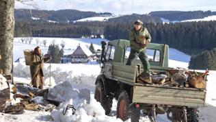 Folge 1048 - Karl wirft Holz von seinem Traktor, Lioba kommt hinter einem Baum hervor, die Landschaft ist schneebedeckt