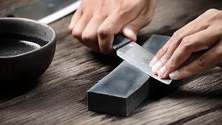 Mann schärft Messer an einem Wetzstein