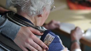 Eine junge Frau hat ihre Hand auf der Schulter einer alten Frau gelegt, die an einem Tisch sitzt.