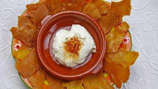 runder Teller mit Tortilla-Chips, in der Mitte ein kleines Tontöpfchen mit heller Creme