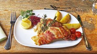 weißer Teller auf Holztisch mit Forelle im Speckmantel mit Cherrytomaten, Kartoffeln und einem Rosmarin-Zweig und einer Zitronenscheibe als Deko. Daneben Messer und Gabel und ein Weinglas.