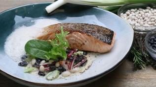 Salat mit weißen und schwarzen Bohnen zu gebratenem Lachsfilet