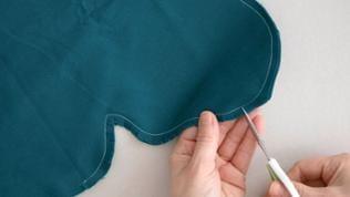 Damit die Rundungen schön herausgearbeitet werden können, wird der Stoff bis knapp an die Naht eingeschnitten.