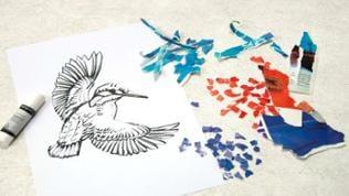 Die Magazinblätter zunächst in grobe, farblich zu sortierende Stücke zerreißen, dann diese zu kleinen Schnipseln verarbeiten und nach Farben geordnet auf dem Tisch bereit legen.