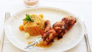 weißer Teller einem Couscous-Timbale und Melonenfleischkugeln daneben, dazu Hühnchenspieße
