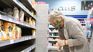Ältere Dame bei einem Einkauf im Supermarkt mit Gesichtsmaske