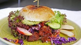 grüner Teller mit einem Burger mit einem Belag aus Jackfruit mit brauner Soße, Apfelscheiben, Salat und Gurke, drumherum Streifen von Rotkohl