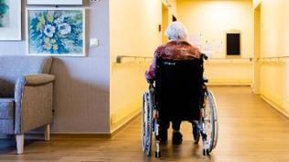 Bewohnerin eines Pflegeheims sitzt in Rollstuhl