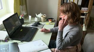 Eine Frau, die telefoniert, sitzt an einem Schreibtisch vor einem Laptop.
