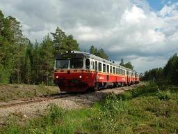 674 Skandinavien: Roter alter Zug mit Wagen im Grünen