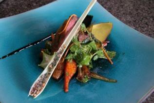 Kunstvoll angerichtetes Gericht auf blauem Teller