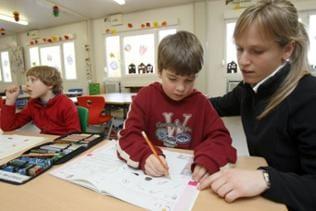 Schüler der ersten Sportgrundschule in Deutschland sitzen unter Aufsicht ihrer Lehrerin in Freiburg in ihrem Klassenzimmer über ihren Heften