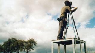 Junger Filmemacher steht auf einem Tisch und filmt