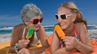 Zwei ältere Frauen liegen am Strand, essen Eis und lachen sich an