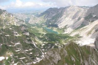 Blick in das von zwei Gebirgszügen umgebene Tal mit seinem See