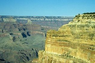 Der Grand Canyon mit seinen unterschiedlichen Farben, rechts eine Felswand in hellem Gelbton links eine Mischung aus grau und rot