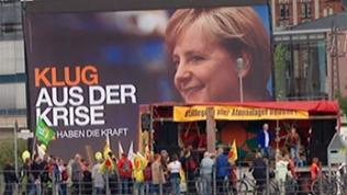 """Atomgegner vor einem großen Merkel-Plakat: """"Klug aus der Krise"""""""