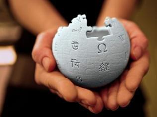 Hand hält 3-Puzzle mit Wikipedia-Logo